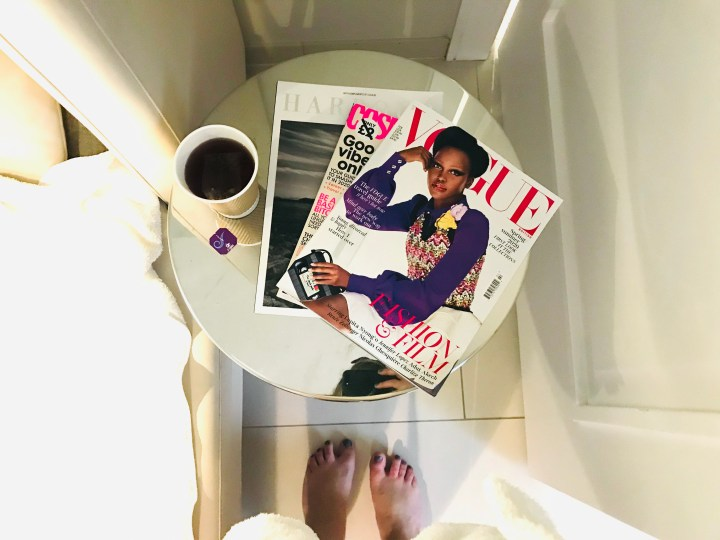 A circle table with a mirror top full of fashion magazines, fruit tea and the photo is taken from above so you can see Bex's feet too.