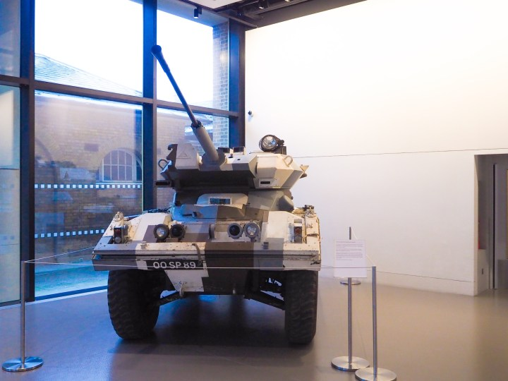 A tank, painted in a camp pattern, in the middle of the museum entrance