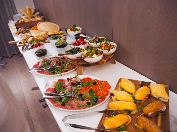 A mediterranean buffet - a table full of hummus, cured meats, olives and arancini.
