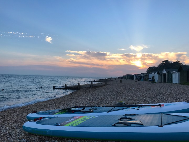Paddle boards on the beach by the Solent with the sun setting
