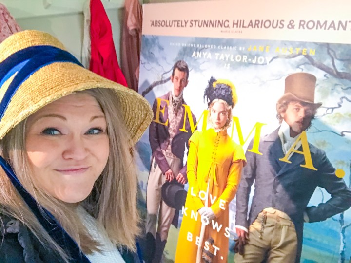 Bex posing in a Jane Austen Bonnet by an Emma film poster