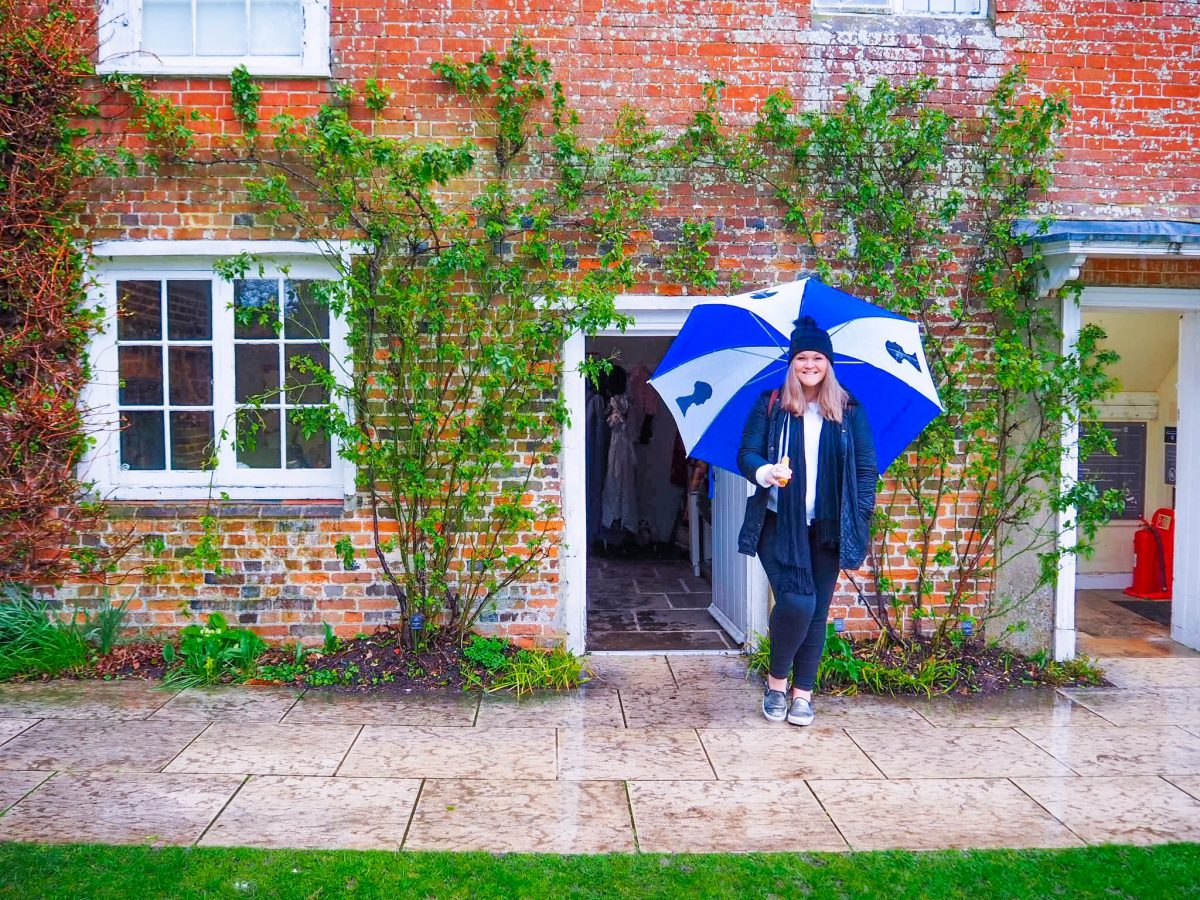 Bex stood in front of the entrance to Jane Austen's House with an umbrella