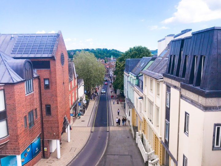 The view from the top of the Westgate Museum, it's of a long straight high street surrounded by historic buildings either side and leafy foliage .