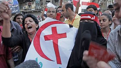 """Muslims and Christians are one hand"" (demonstrators have cross & crescent)"