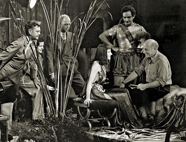 Left to right: Karl Struss; unidentified script clerk; Mitchell Leisen, Claudette Colbert, Fredric March, and Cecil B. DeMille. Besides acting as production designer, Leisen designed both this set and Claudette Colbert's costume. Leisen prepared the scene so that every cut showed a fresh angle.