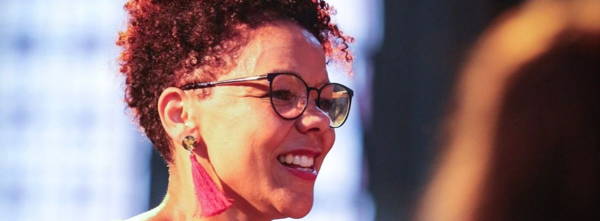 A photo of Amanda Mitchell, the Director of Bright Soul Choir & Events. She has brown skin, round dark blue glasses and short hair. She is wearing a short sleeved grey top, dangly red ear rings. She looks animated and is grinning.