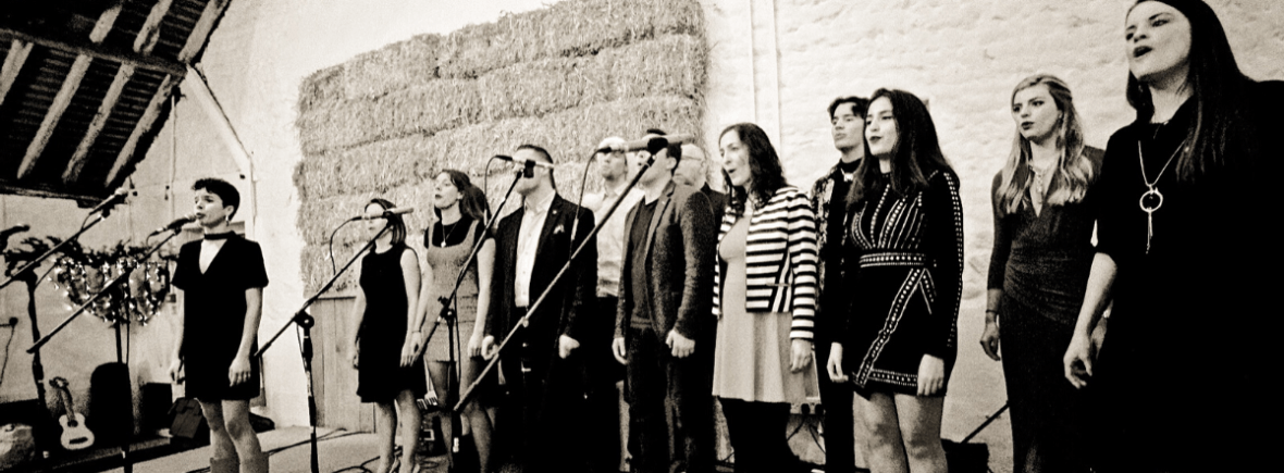 This is a black and white photo of Brand watch employees performing on stage.