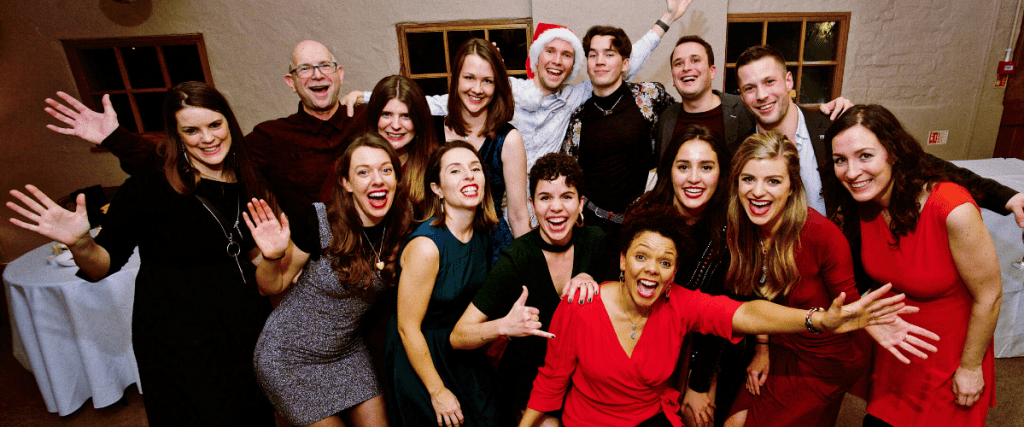 A colour photo of Employees of Brandwatch after their first performance as a choir. They are smiling and laughing, some with their hands in the air. They are all smartly dressed.