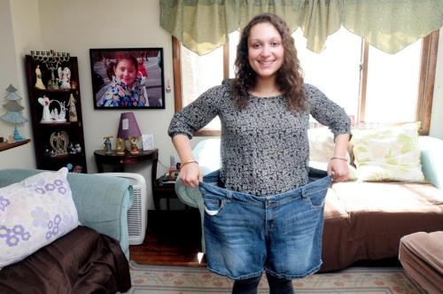(Arnold Gold-New Haven Register) University of Rhode Island senior Brianna Blank, 21, is photographed in the living room of her home in Westbrook on 4/12/2014 with a pair of shorts she wore when she was 150 pounds heavier.