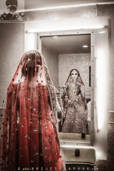 Indian Bride getting ready before her wedding. standing in front of the mirror. wearing a red lehenga choli. photo captured by Brijesh Kapoor