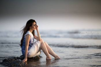 GERMAN MODEL SITTING ON KASHID BEACH IN ALIBAG MUMBAI WEARING A WHITE AND BLUE FLORAL DRESS BEING PHOTOGRAPHED BY BRIJESH KAPOOR PHOTOGRAPHY