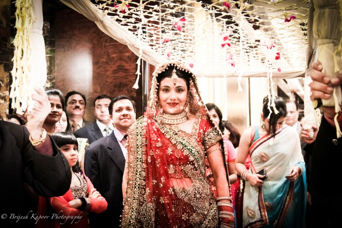 INDIAN BRIDE WALKING DOWN THE AISLE WEARING A RED LEHENGA DURING A BIG FAT INDIAN WEDDING SHOT BY BRIJESH KAPOOR PHOTOGRAPHY