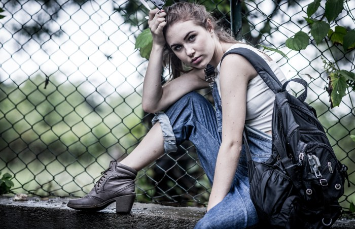 MODEL WEARING A DENIM DUNGAREE WITH A WHITE CROP TOP AND A BLACK BACKPACK GETTING HER PHOTOSHOOT DONE BY BRIJESH KAPOOR PHOTOGRAPHY