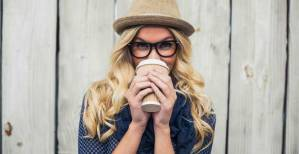 Smiling-fashionable-blonde-drinking-coffee-outdoors