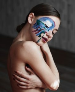 performer with painted face holding herself tenderly