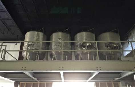 Fermentation tanks located on a mezzanine level.