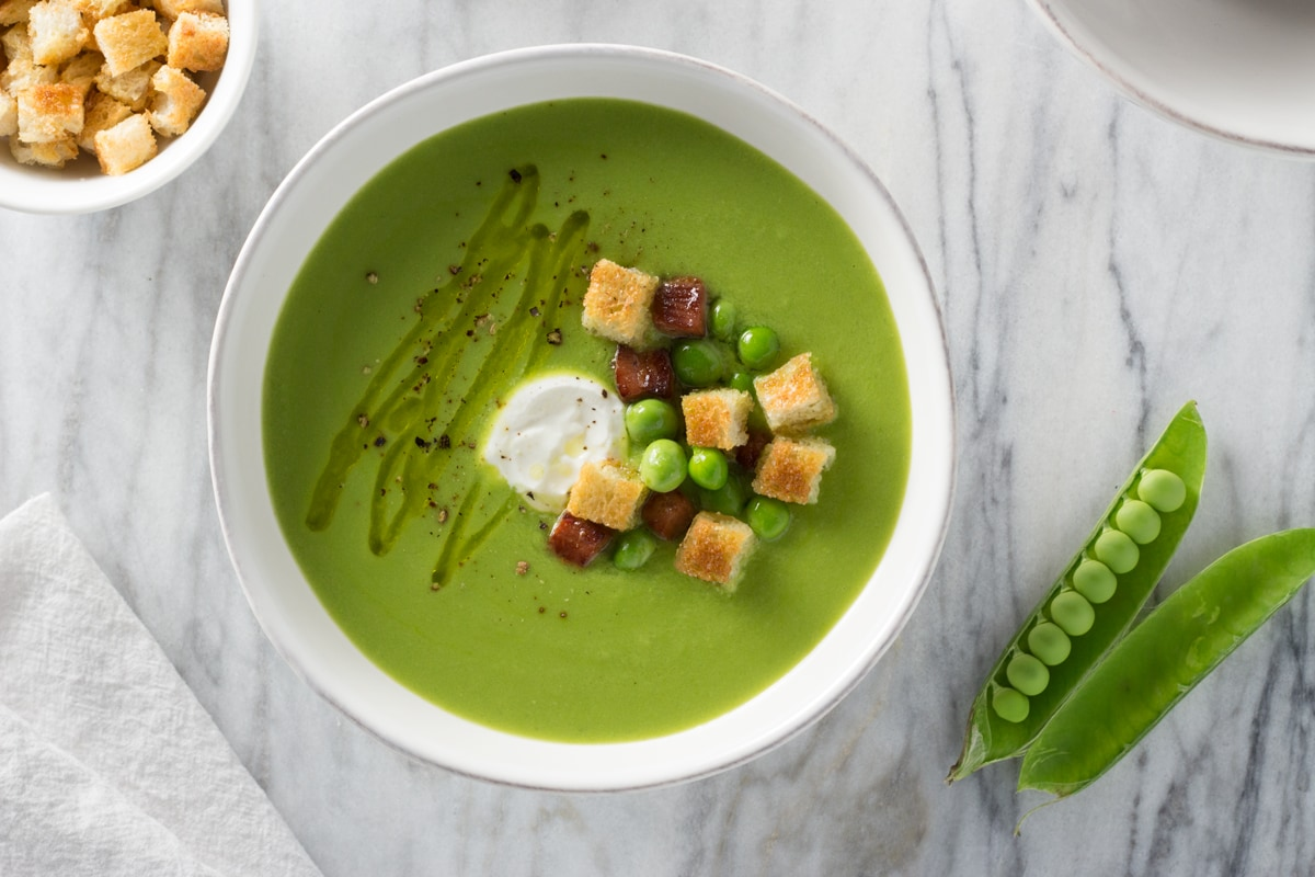 Overhead view of green pea soup topped with creme fraiche, pancetta, croutons, and fresh peas.