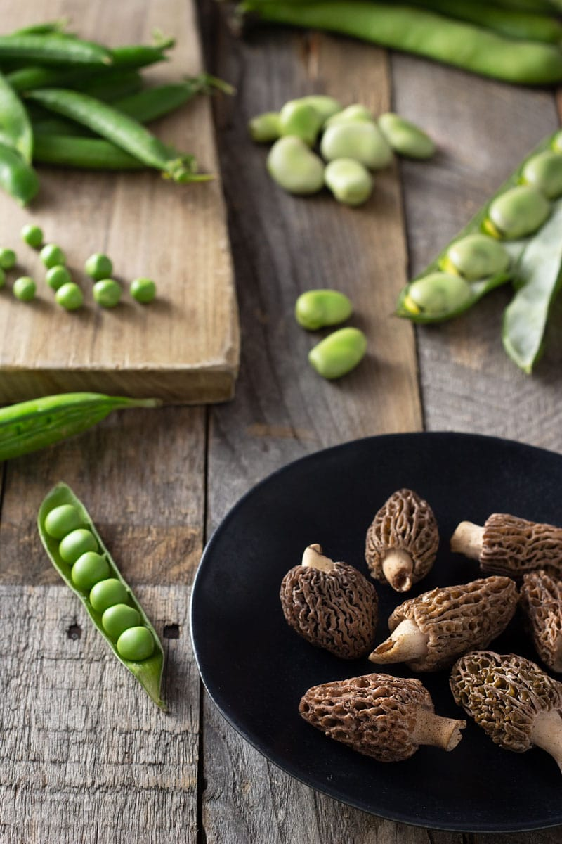 Angled shot of raw morel mushrooms, peas in the pod, and fresh fava beans with a light wood cutting board and a grey wood surface.