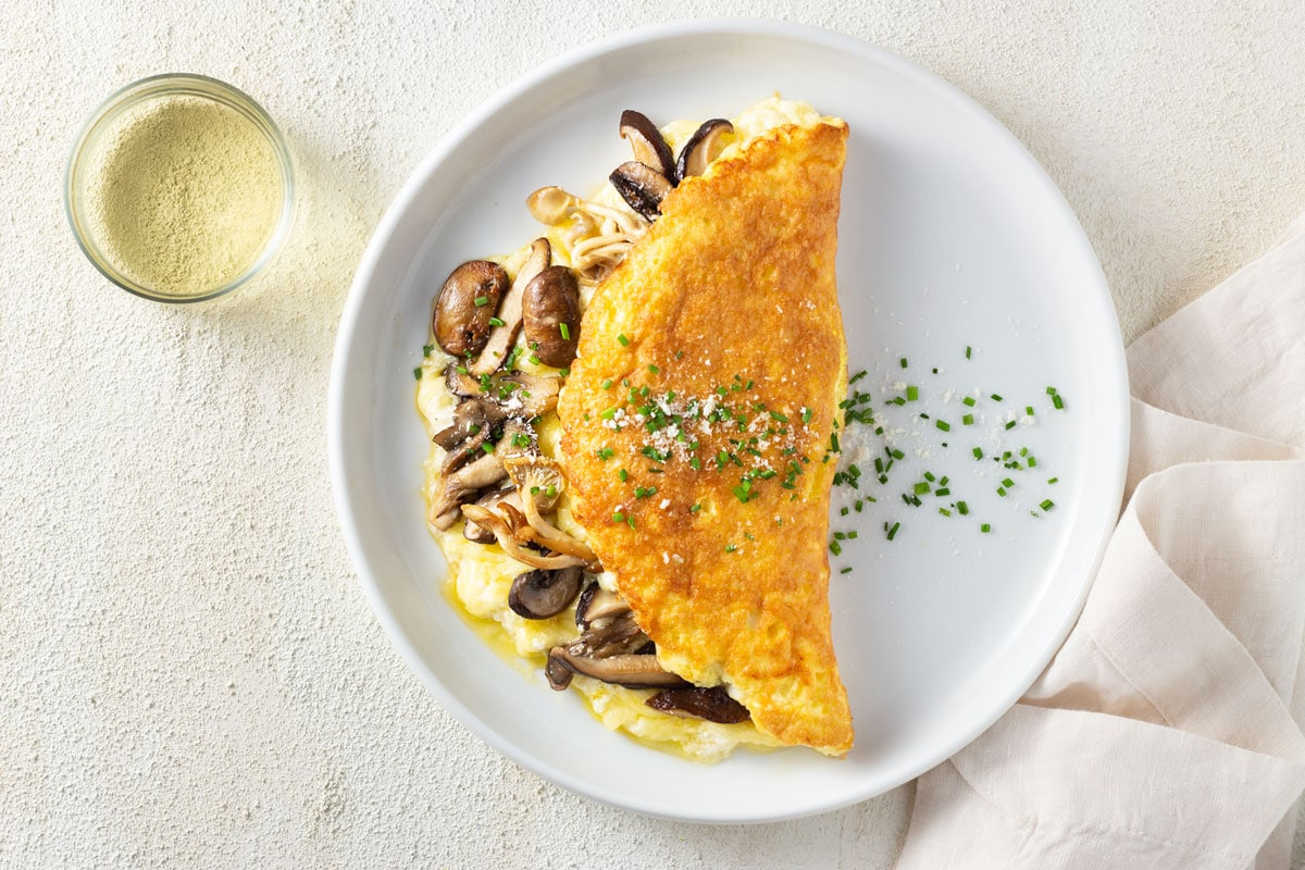 Overhead view of a souffle omelet filled with parmesan cheese, gruyere cheese and mixed mushrooms and topped with chives and parmesan. It's on a white plate with an off white, textured surface, a glass of white wine and an off white towel.