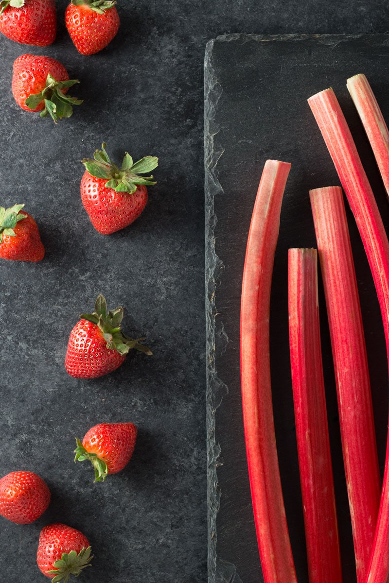 Raw rhubarb and whole strawberries on a dark grey and slate surface.