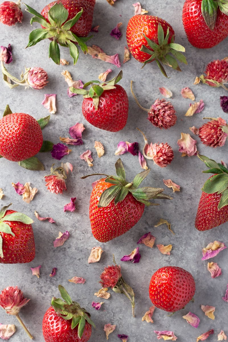 Overhead shot of fresh strawberries and dried rose petals and flower buds on a light grey textured surface.
