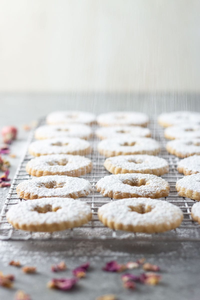 3/4 angle shot of linzer cut out cookie tops being dusted with powdered sugar on a cooling rack on a light grey surface and light backdrop surrounded by dried rose petals.
