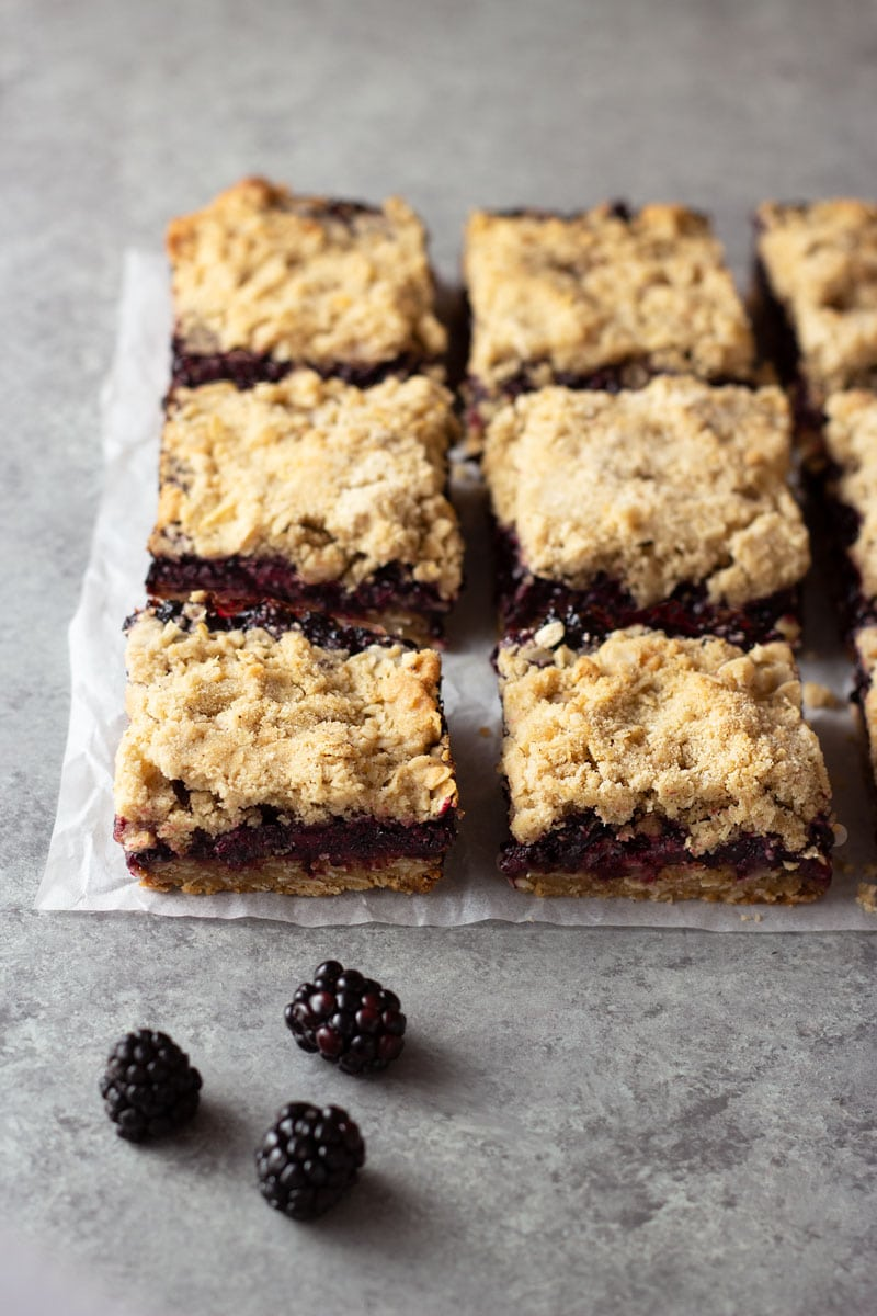 3/4 shot of blackberry crumb bars on parchment paper on a light grey surface surrounded by fresh blackberries.