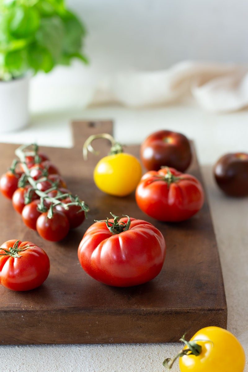 Multi-colored heirloom tomatoes on a dark wood French cutting board on an off white, textured surface with a basil plant and a white dish towel in the background.