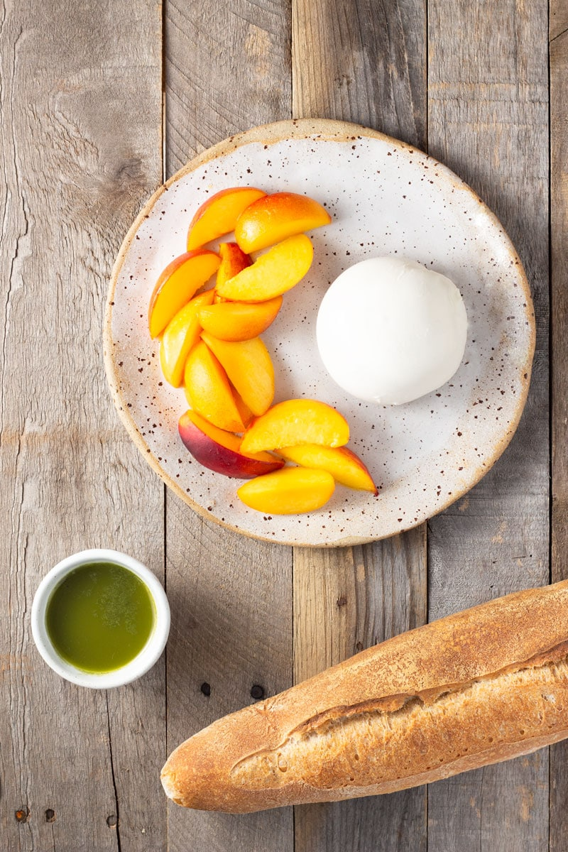 Overhead shot of a rustic plate of sliced peaches and burrata cheese, surrounded by a bowl of basil oil and baguette bread on a rustic, light wood surface.