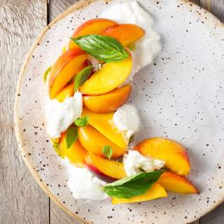 Overhead shot of a rustic plate of sliced peaches, burrata cheese and basil, surrounded by sliced bread and a bowl of basil oil on a rustic, light wood surface.
