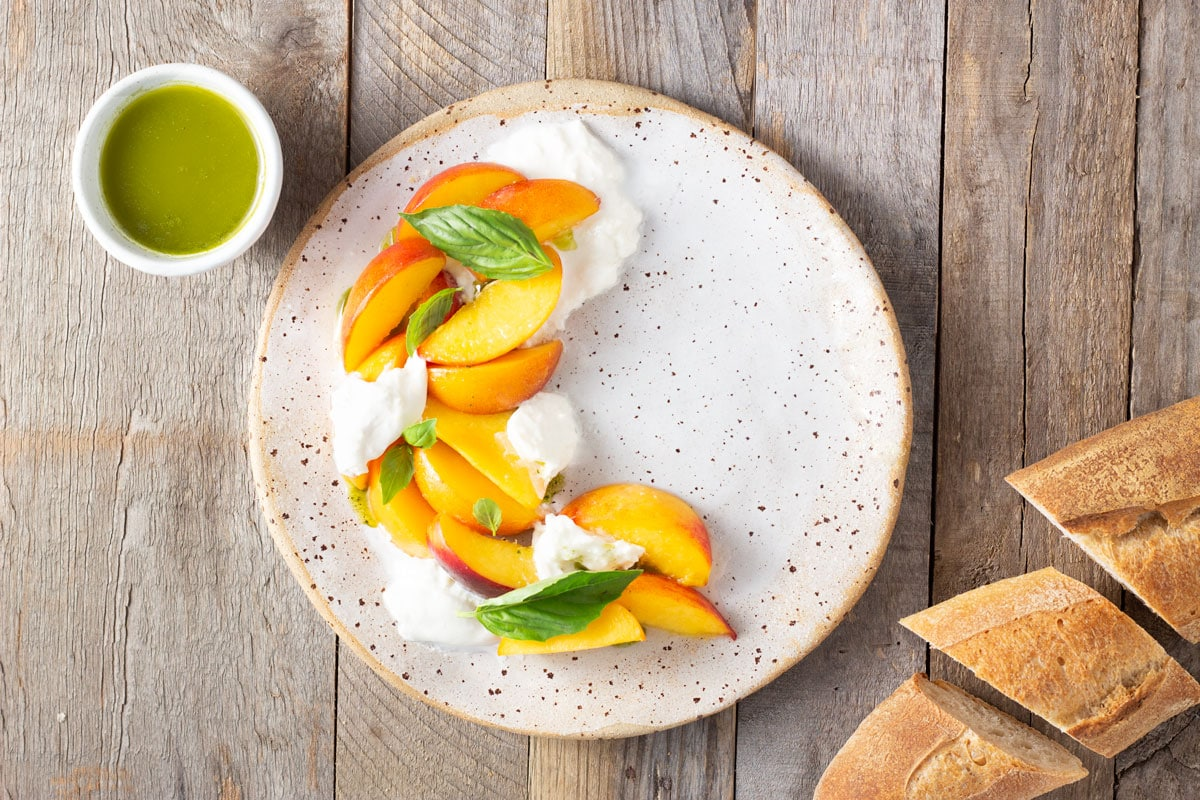 Overhead shot of a rustic plate of sliced peaches, burrata cheese and basil oil, surrounded by sliced bread and a bowl of basil oil on a rustic, light wood surface.