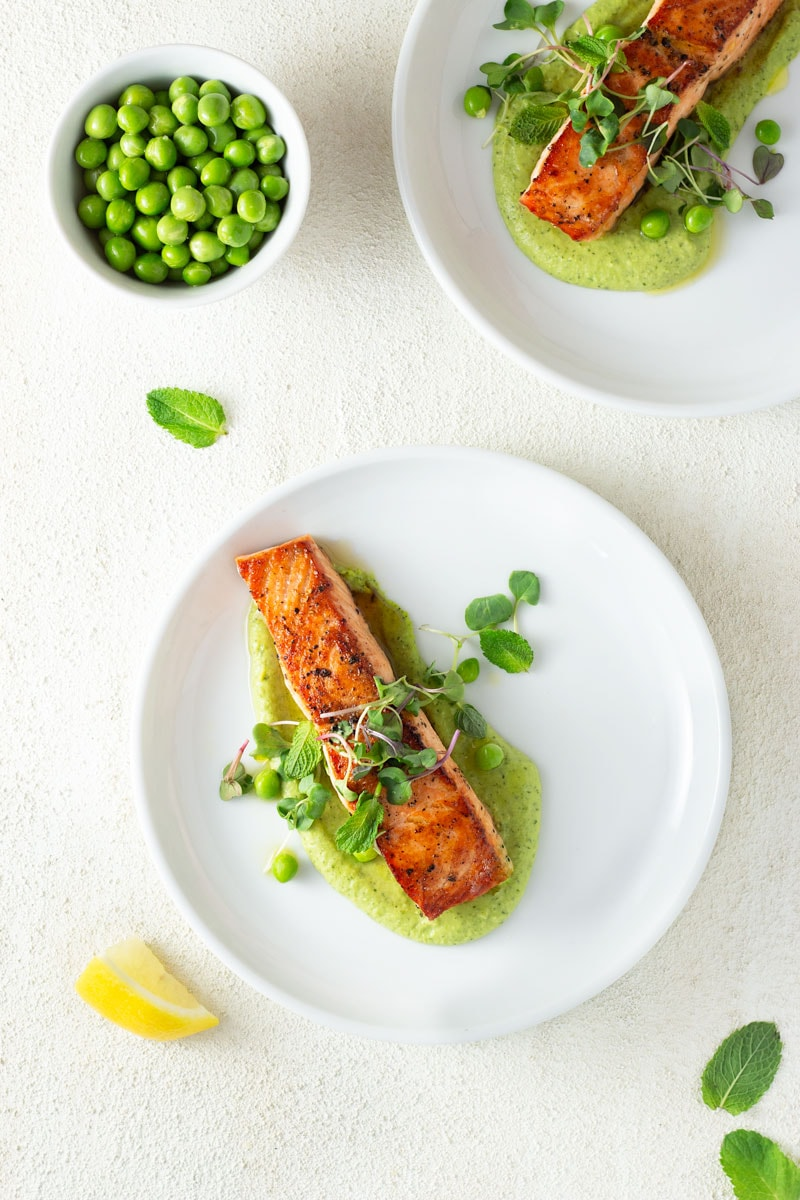 Overhead shot of two plates of seared salmon over spring pea puree with mint and yogurt, topped with microgreens, mint and raw peas, surrounded by a bowl of raw peas, mint leaves and a lemon wedge with white plates on a white, textured surface.