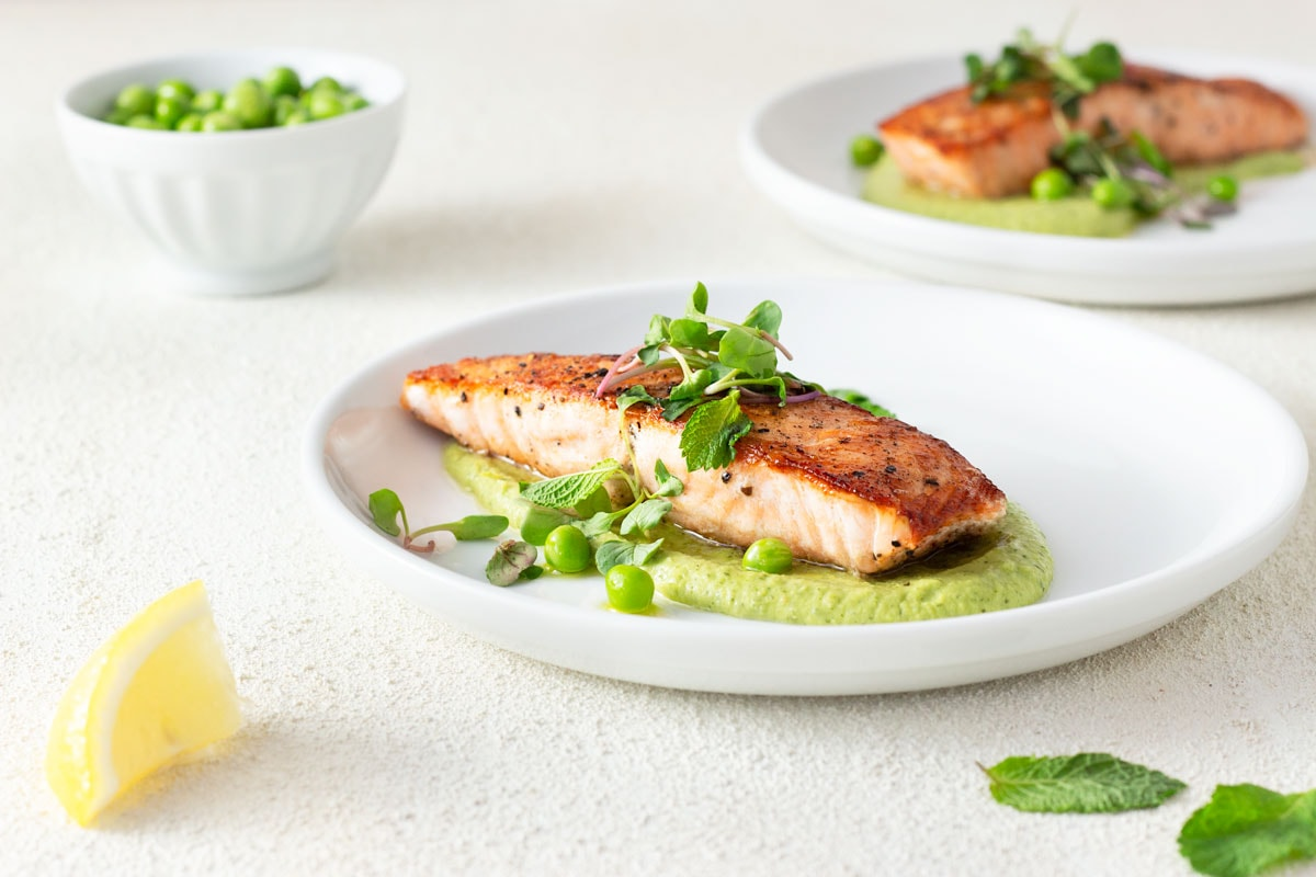 Straight on shot of two plates of seared salmon over spring pea puree with mint and yogurt, topped with microgreens, mint and raw peas, surrounded by a bowl of raw peas, mint leaves and a lemon wedge with white plates on a white, textured surface.