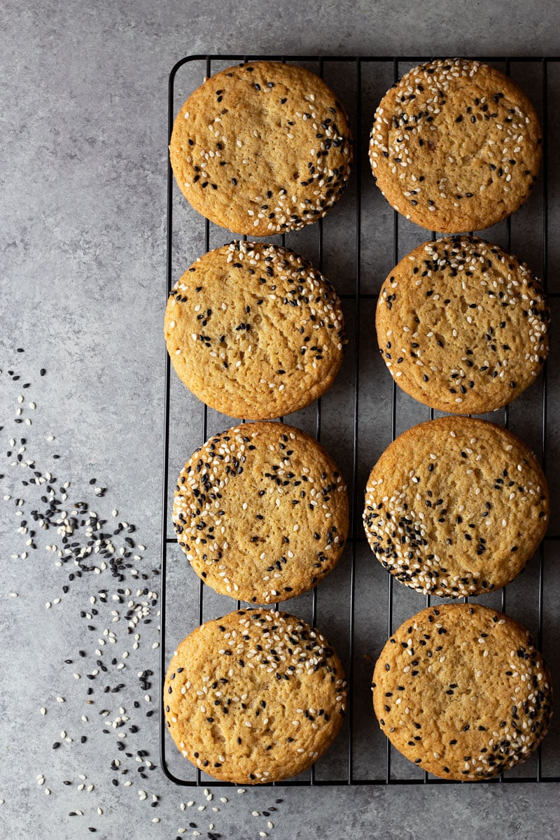 Overhead shot of sesame tahini cookies topped with black and white sesame seeds on a black cooling rack on a light grey, textured surface.