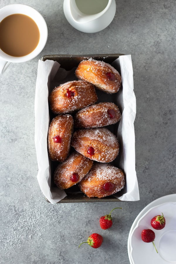 Overhead shot of homemade jelly doughnuts with strawberry jam in a loaf pan surrounded by dessert plates, a cup of coffee, a milk pitcher and and fresh strawberries on a light grey, textured surface.