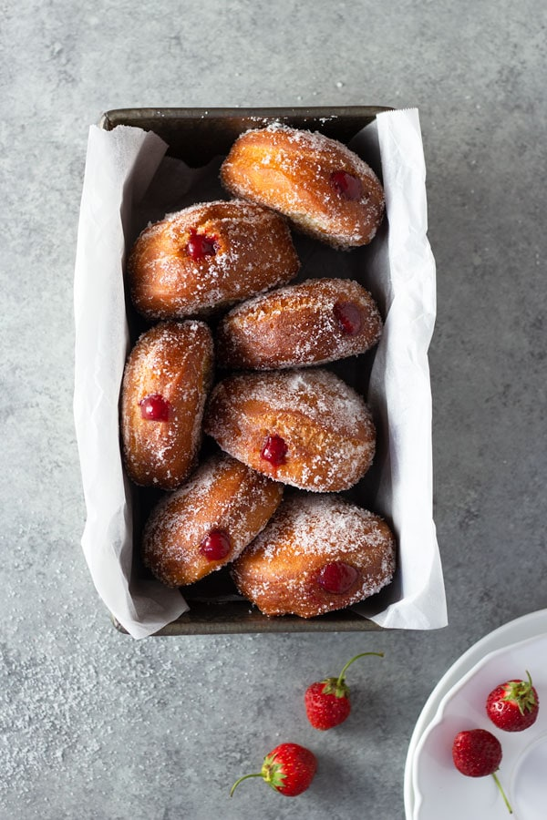Overhead shot of homemade jelly doughnuts with strawberry jam in a loaf pan surrounded by dessert plates and fresh strawberries on a light grey, textured surface.