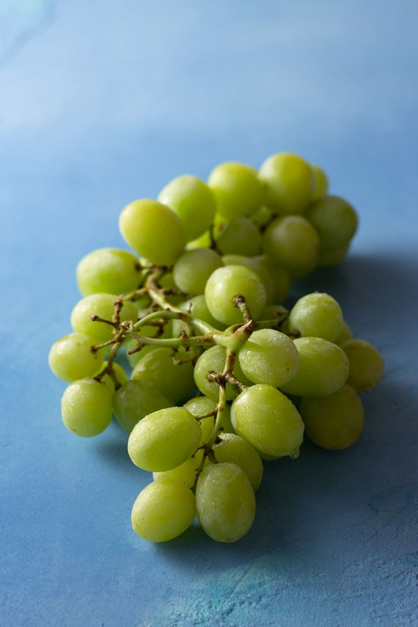 3/4 shot of green grapes misted with water on a bright blue, textured surface.