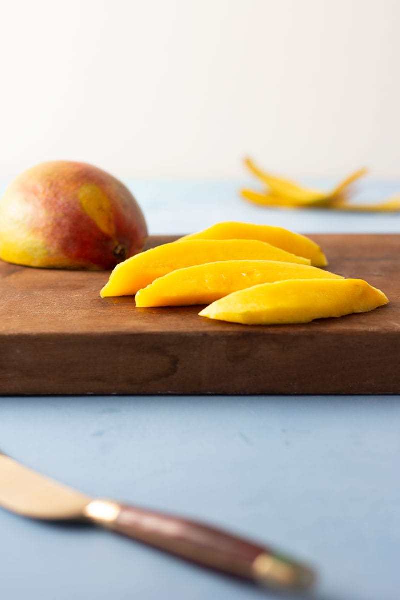Straight on shot of sliced mango on a dark wood cutting board on a bright blue, textured surface surrounded by a knife, a half mango, and mango skins.