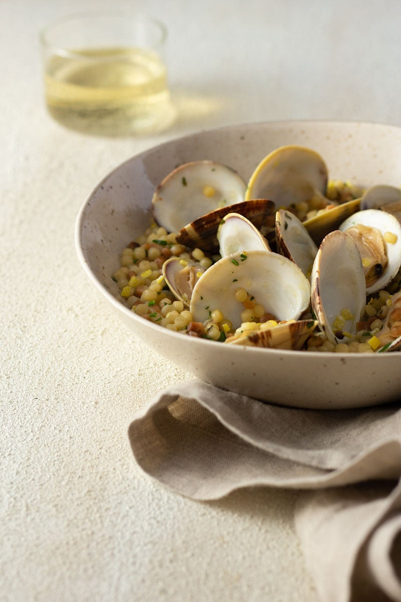 3/4 angled shot of a light, rustic bowl of fregola pasta with clams surrounded by a glass of white wine and a neutral colored towel on a light, cream colored, textured plaster surface.
