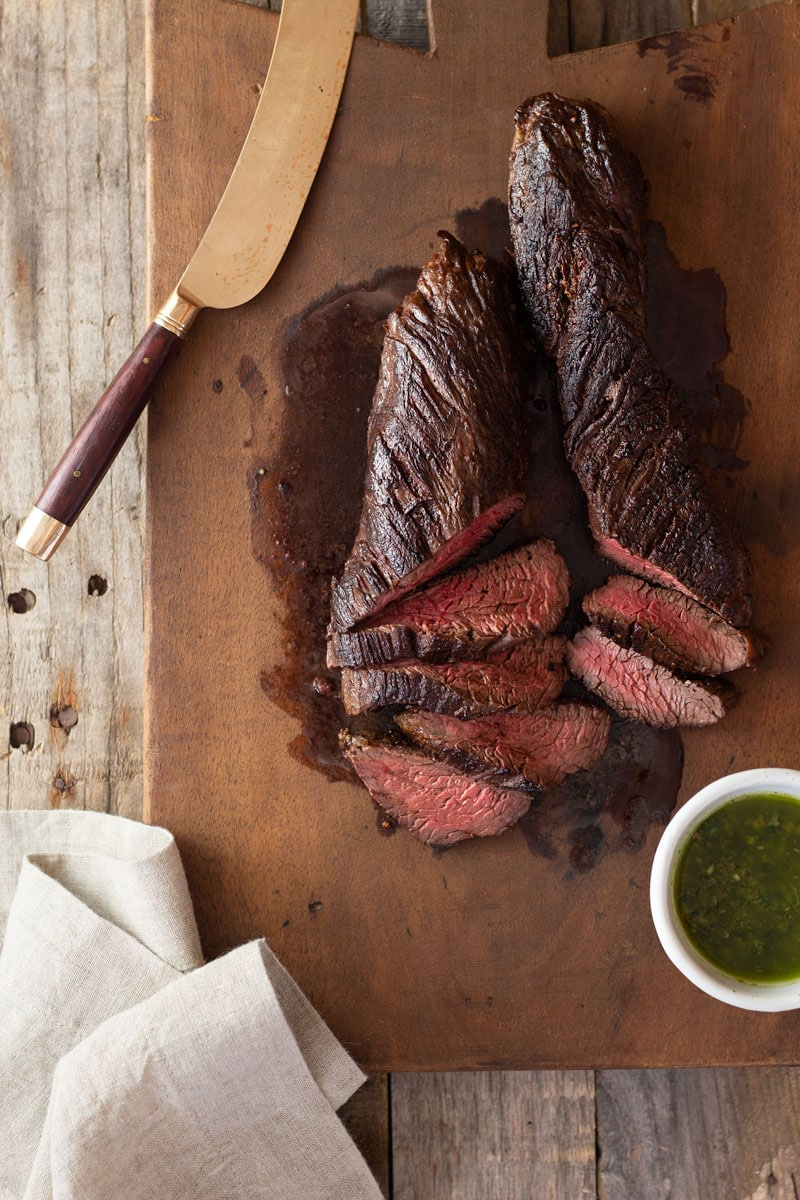 Overhead view of partially sliced hanger steak on a vintage, French wood cutting board surrounded by a gold meat knife, a small bowl of Italian salsa verde and a dish towel on a light, rustic wood surface.