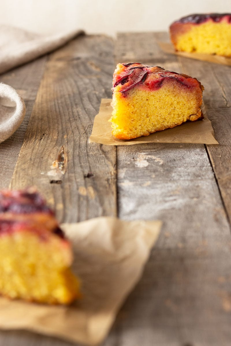 Straight on shot of three slices of Polenta (cornmeal) Plum Upside Down Cake on squares of brown parchment surrounded by a beige dish towel on a light grey, wood surface.