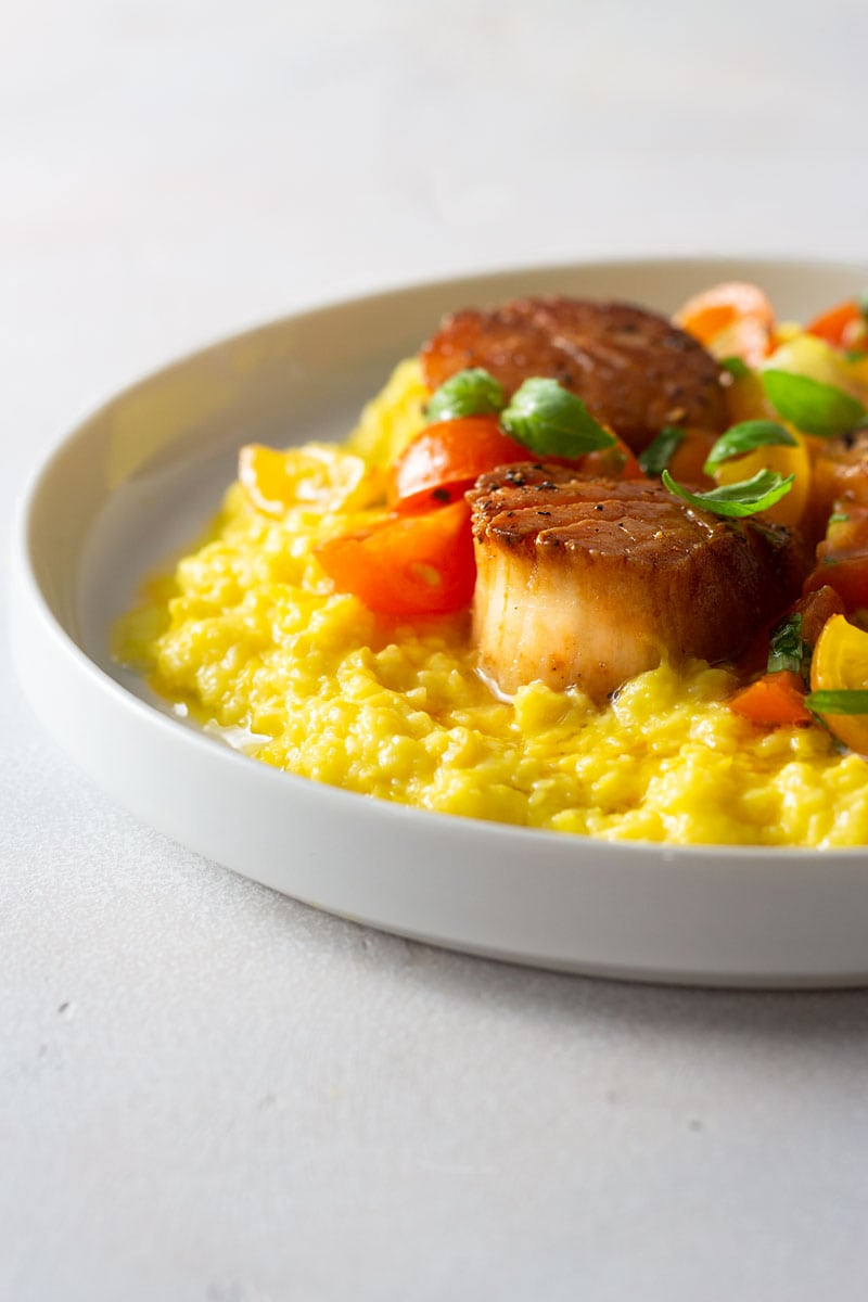 Straight on shot of creamed corn topped with seared scallops and fresh sungold tomatoes with tarragon and basil on a white plate on a light, textured background.