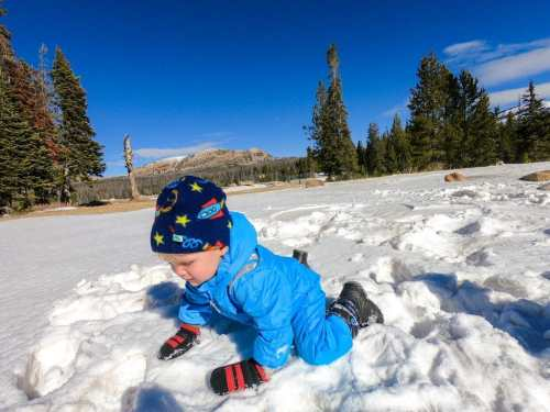 baby crawling in snow wearing mittens and snow boots