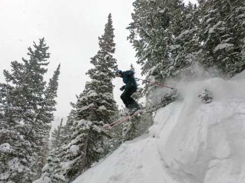 man jumping off cliff with skis