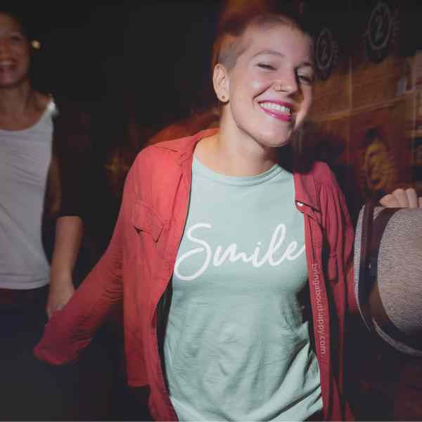 A woman walking and holding the hand of someone else while wearing a mint green shirt that says smile
