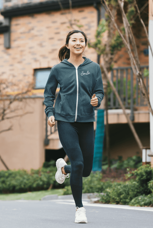 A woman running while wearing a blue jay color zip hoodie with smile written on the front