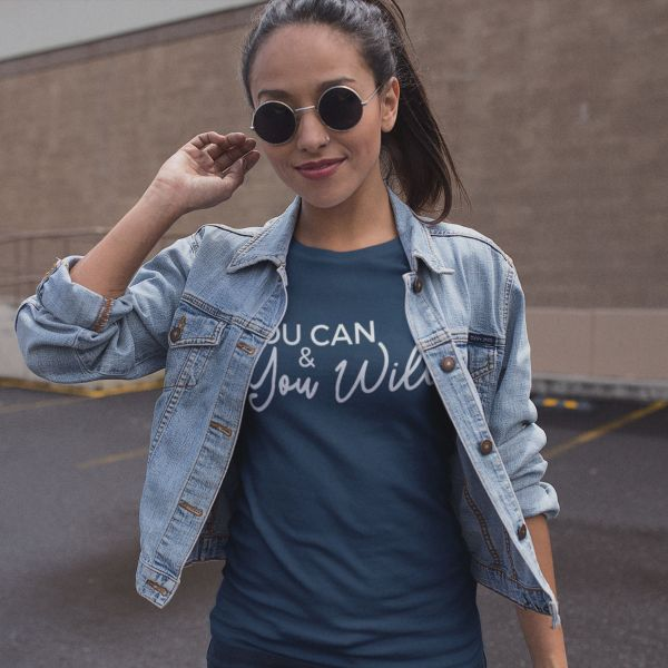 A woman wearing a blue You Can & You Will shirt with a jean jacket and glasses on