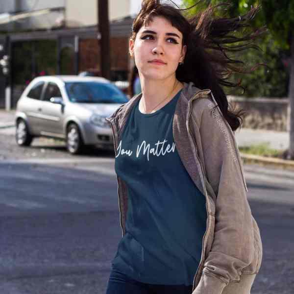 Woman crossing the street wearing an indigo blue you matter shirt