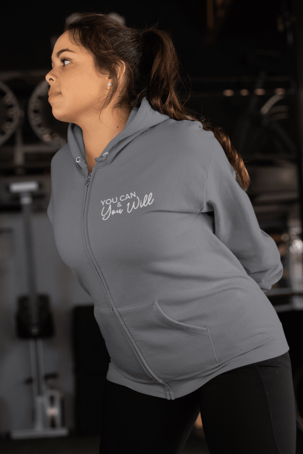 A woman stretching while wearing a mink gray you can and you will zip hoodie sweatshirt