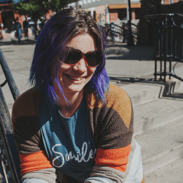 A smiling woman with short hair wearing a Smile Classic Fit TShirt in indigo